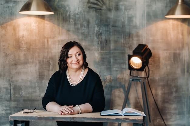 Деловая женщина в черном платье с бусами стоит за столом в своем офисе.
