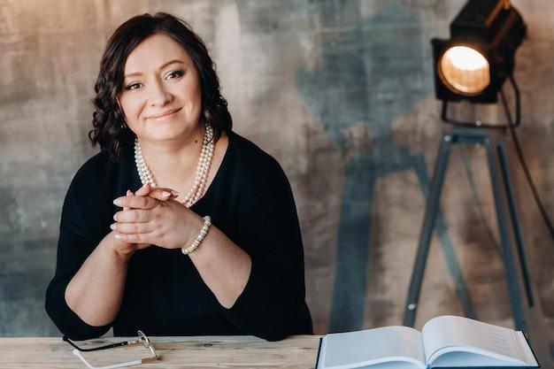 ビーズの黒いドレスを着た実業家が彼女のオフィスの机に立っています。