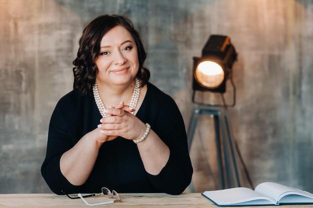 Деловая женщина в черном платье с бусами стоит за столом в своем офисе