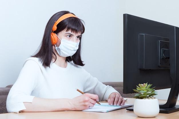 Деловая женщина в медицинской маске и наушниках делает онлайн-видеозвонок с пациентом, подписывает документ в своем офисе