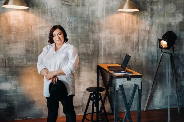 Деловая женщина в белой рубашке и брюках стоит в своем офисе.
