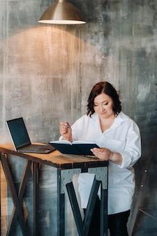 Деловая женщина в белой рубашке сидит за столом и пишет что-то в блокноте в офисе.