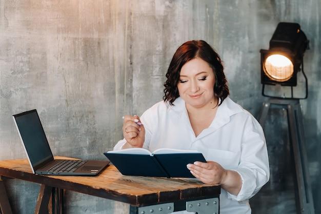 白いシャツを着た実業家が机に座って、オフィスのノートに何かを書いています。