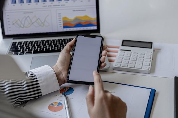Деловая женщина держит смартфон и с его помощью отправляет текстовые сообщения партнеру компании о финансовых отчетах. концепция использования технологий в общении.