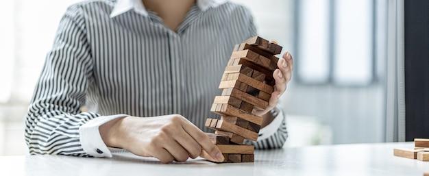 実業家は、良いビジネスを営んだり問題を解決したりするように、落ちないように機能している木製のブロックを支えています。リスクに関する経営管理の概念。