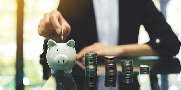 お金と金融の概念を節約するためにテーブルの上のコインスタックで貯金箱にコインを置く実業家