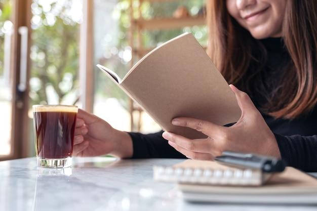 Деловая женщина читает книгу, попивая кофе в кафе