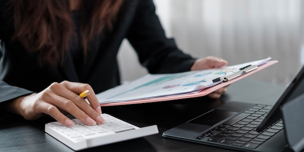 Деловая женщина, использующая калькулятор и держащая деньги для расчета налога в офисе