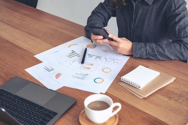 オフィスのテーブルでビジネス文書やノートパソコンの作業中に携帯電話を使用している実業家