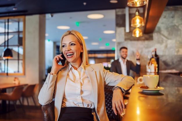 ポジティブなエネルギーを持ったビジネスウーマンがコーヒーブレイクのためにカフェに座って電話をかけます。電気通信、自由時間、休憩、ソーシャルネットワーク