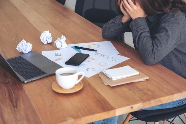 Деловая женщина, работающая с разочарованием и стрессом из-за испорченных бумаг и ноутбука на столе в офисе