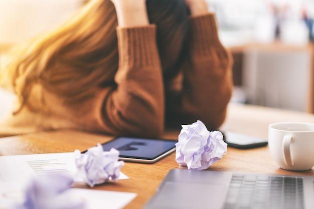 사무실 탁자 위에 있는 엉망인 서류와 노트북으로 좌절감과 스트레스를 받고 일하는 여성