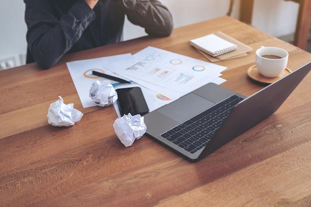 Деловая женщина, которая чувствует себя неудачницей и страдает от испорченных бумаг и ноутбука на столе в офисе