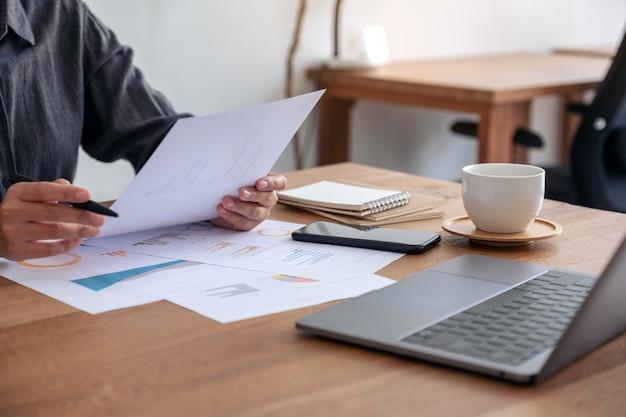 Деловая женщина, пишущая и работающая над бизнес-данными и документом с ноутбуком на столе в офисе