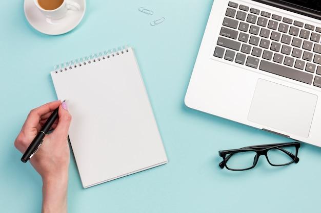 オフィスの机の上のスパイラルメモ帳に書いて実業家