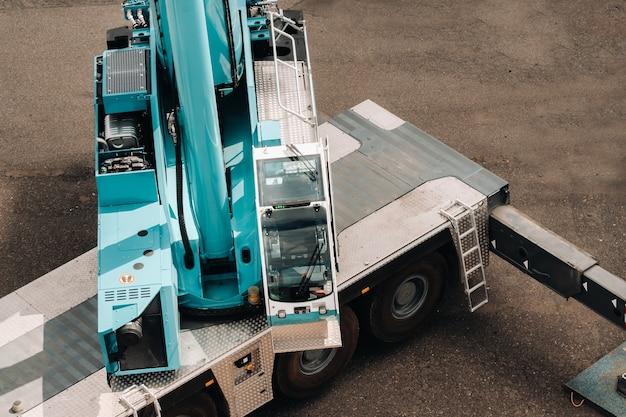 대형 현대식 건물 옆 플랫폼의 유압 지지대에서 작동 할 준비가 된 대형 파란색 자동차 크레인 운전자가있는 운전실. 복잡한 작업을 해결하기위한 가장 큰 트럭 크레인.