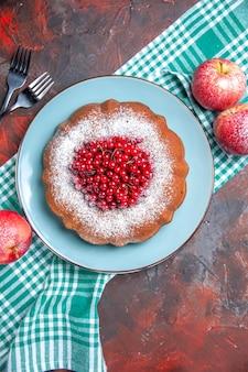 フォークの横にある白青のテーブルクロスにケーキ赤いリンゴのケーキ