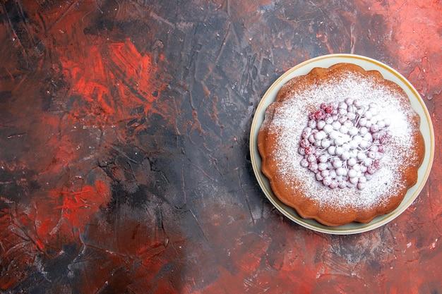 하얀 접시에 붉은 건포도와 가루 설탕을 넣은 케이크