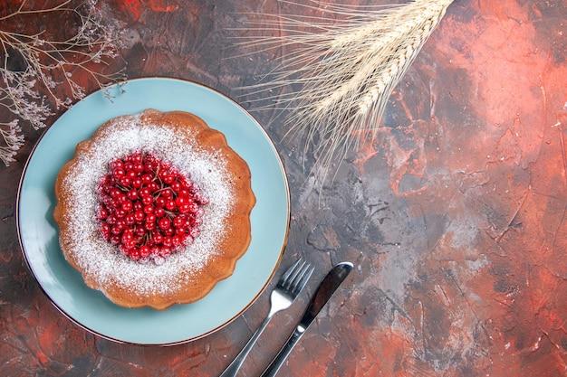 ケーキプレートに赤スグリのケーキ枝ナイフとフォーク
