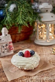 懐中電灯とトウヒの枝のあるクリスマステーブルにブラックベリーとラズベリーで飾られたケーキ。垂直フレーム