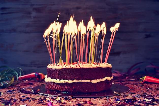 素朴な木製のテーブルでケーキを吹き消す前に、いくつかの火のともったろうそくをトッピングしたケーキ