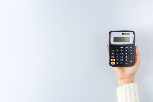 Калькулятор в руке на белой стене. - экономия денег на концепции финансового учета.
