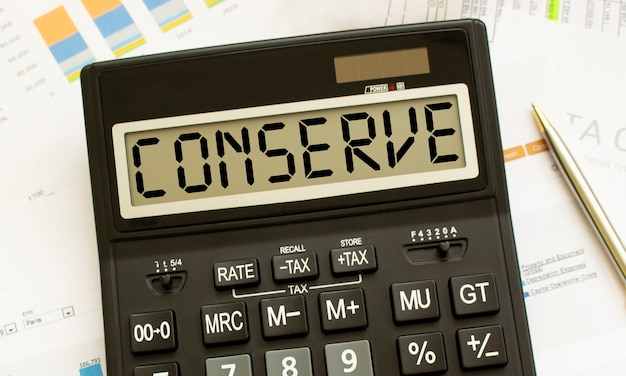 Калькулятор с надписью conserve лежит на финансовых документах в офисе. бизнес-концепция.