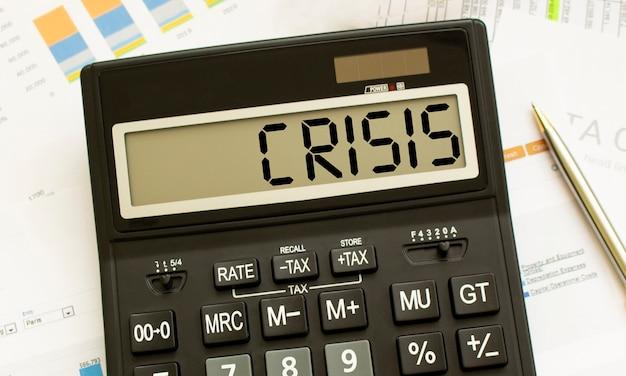 Калькулятор с надписью crisis лежит на финансовых документах в офисе.