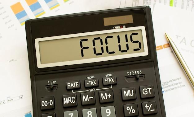 Focusというラベルの付いた計算機は、オフィスの財務書類にあります
