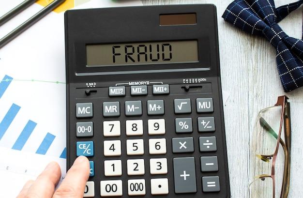 Калькулятор с надписью мошенничество лежит на финансовых документах в офисе.