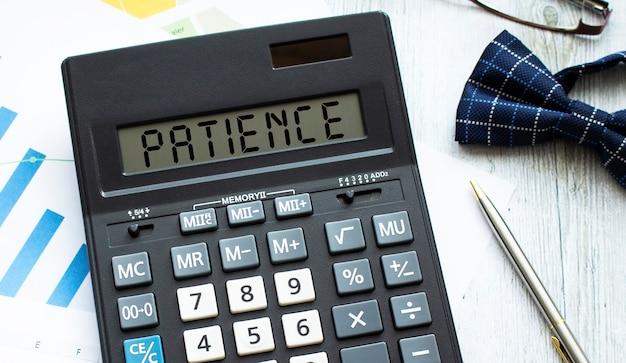 Калькулятор с надписью терпение лежит на финансовых документах в офисе. бизнес-концепция.