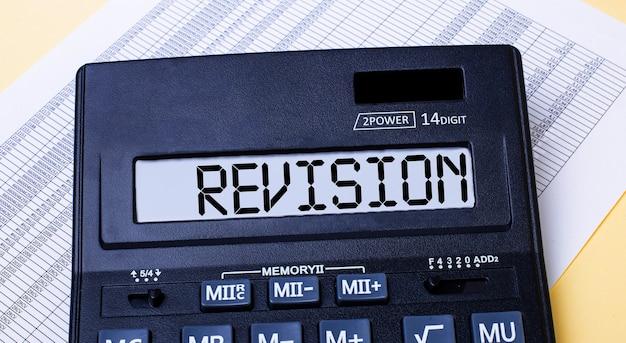 Калькулятор с надписью revision находится на столе рядом с отчетом. финансовая концепция
