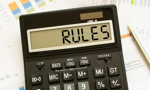 Калькулятор с надписью правила лежит на финансовых документах в офисе.