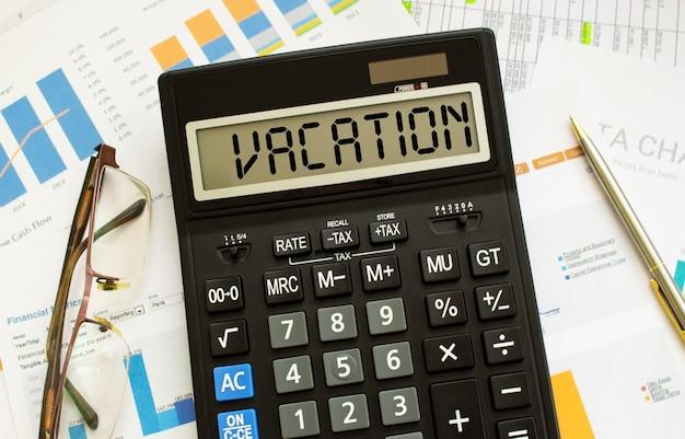 Калькулятор с надписью отпуск лежит на финансовых документах в офисе.