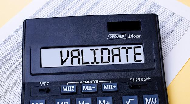Калькулятор с надписью validate находится на столе рядом с отчетом. финансовая концепция