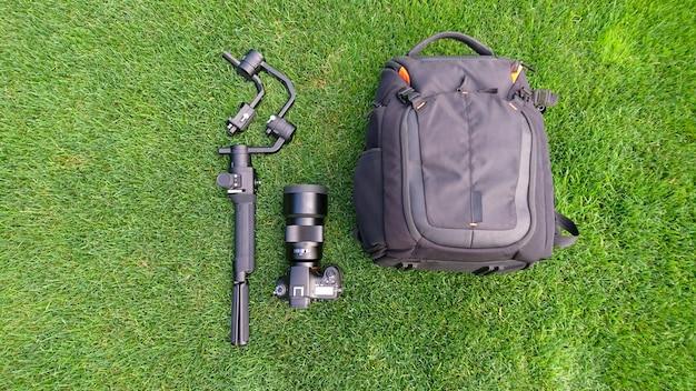 Фотоаппарат, сумка, подвес и оборудование для видеопроизводства на пышной траве, фоне дерна.