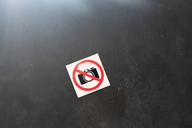 Наклейка с изображением запрещенного символа камеры на стене в общественном месте в зоне ограничения съемки.