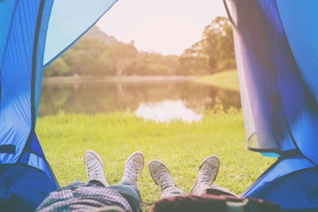 캠핑 텐트는 남자와 여자의 수면에서 빛을 발하며 강 숲이있는 산을 바라보고 있습니다.