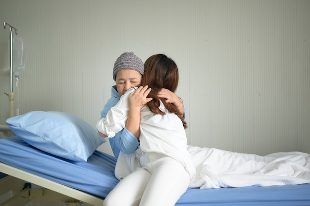 Женщина больного раком, носящая головной платок, обнимает ее поддерживающую дочь в помещении, концепции здравоохранения и страхования.