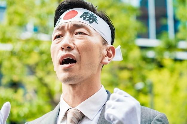 彼らの声を上げるためにヘッドバンドで選挙の候補者。ヘッドバンドに書かれている文字は日本語で、意味は「必ず勝つ」です。