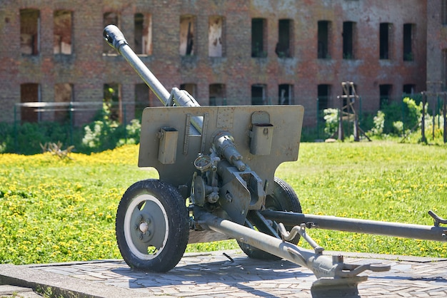 Пушка времен второй мировой войны на фоне разрушенного здания из красного кирпича