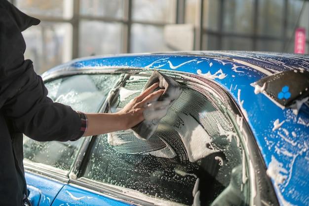 자세히 설명하는 자동차, 스폰지를 들고 손을 닫고 차를 청소