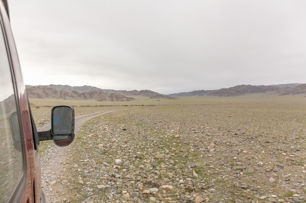モンゴルの草原の曲がりくねった道を走る車。車の窓から撮った写真
