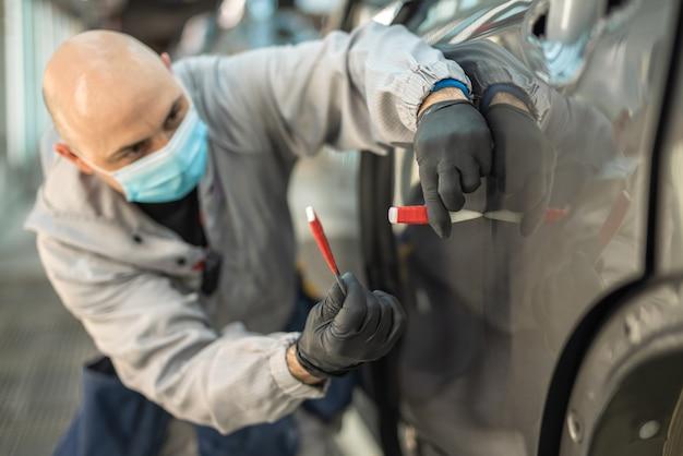 保護用医療マスクを着用した自動車工場の労働者が小さな欠陥を修正