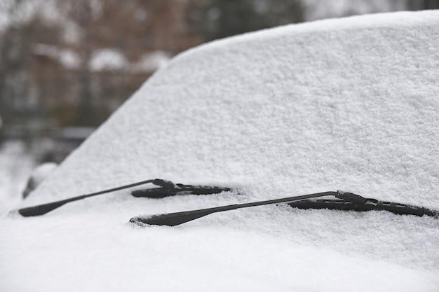 最初の秋の雪の中の田舎道の車。田舎道で最初の冬の雪、雪の下の車。車のスノーワイパーワイパー