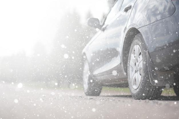 最初の秋の雪の中の田舎道の車。田舎道で最初の冬の雪、雪の下の車。
