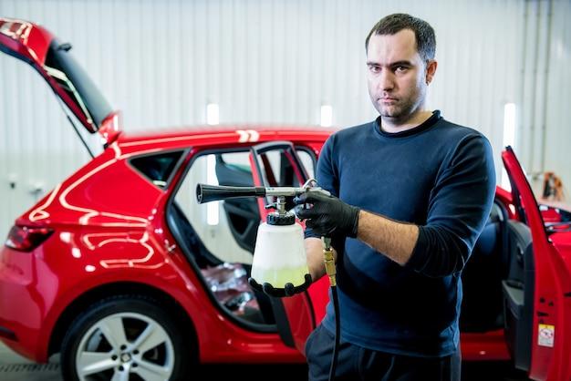 Работник автосервиса чистит салон специальным пеногенератором.