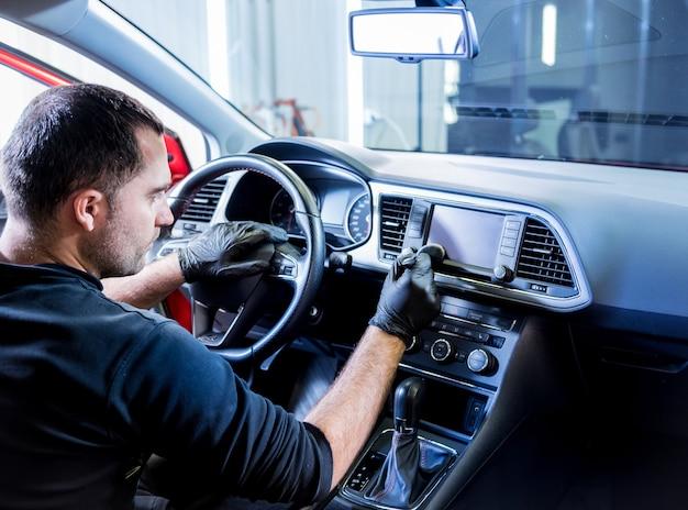자동차 서비스 작업자가 특수 브러시로 자동차 콘솔을 청소합니다.