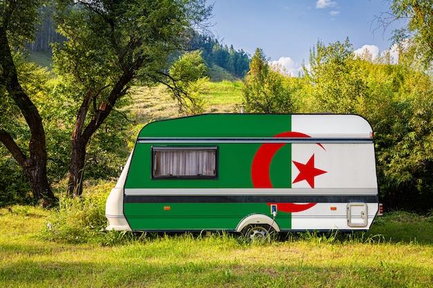 Автомобильный прицеп, дом на колесах, окрашенный в национальный флаг алжира, стоит на стоянке в гористой местности.