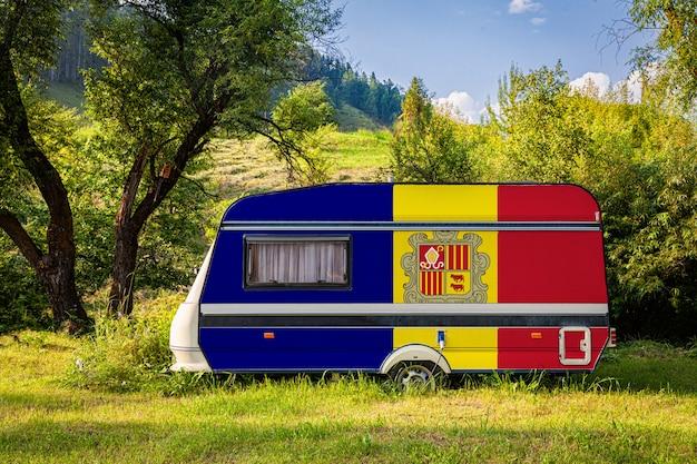 Автоприцеп, дом на колесах, окрашенный в национальный флаг андорры, стоит на стоянке в гористой местности.